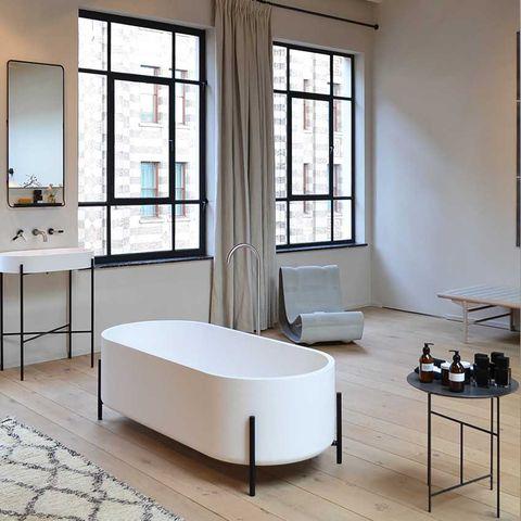 Monochrome bathroom, white sanitary-ware on black frames with oak floor