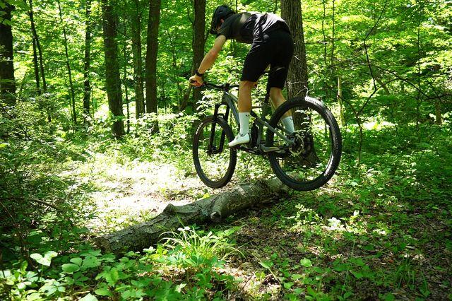 mountain biker bunny hopping a log