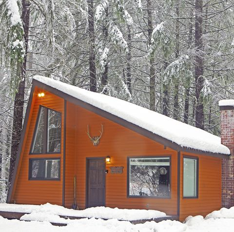 orange cabin in the woods in winter