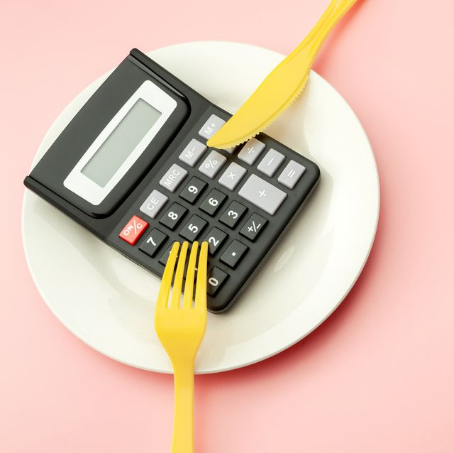 calculate expensive food spending costs, counting calories and weight loss program concept with calculator on empty plate, yellow fork and knife isolated on pink background with copy space