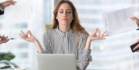 Calm female executive meditating taking break avoiding stressful job