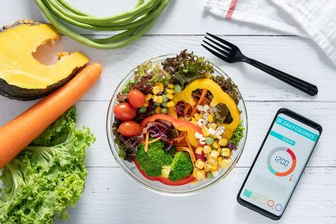 calories counting , diet , food control and weight loss concept calorie counter application on smartphone screen at dining table with salad, fruit juice, bread and vegetable