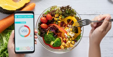 calories counting , diet , food control and weight loss concept calorie counter application on smartphone screen at dining table with salad, fruit juice, bread and fresh vegetable healthy eating