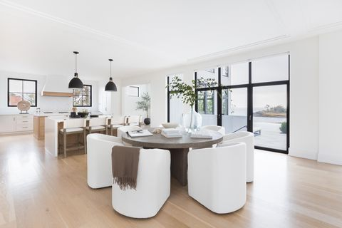 Wooden dining table, white chairs, books with coffee tables