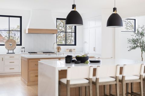 white kitchen, wooden cupboards, white bar stools, white countertops, black ceiling lamps