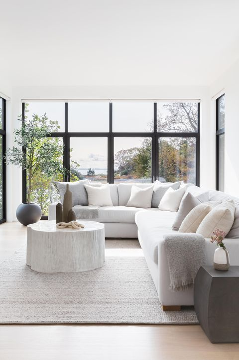 gray couch, wooden coffee table, gray carpet, gray throw, glass doors