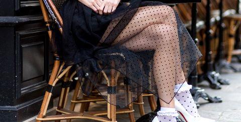 Street fashion, Clothing, Eyewear, Sitting, Fashion, Shoulder, Footwear, Leg, Fashion model, Joint,