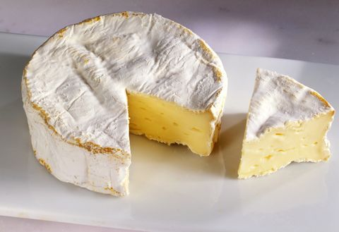 Camembert cheese with wedge cut out