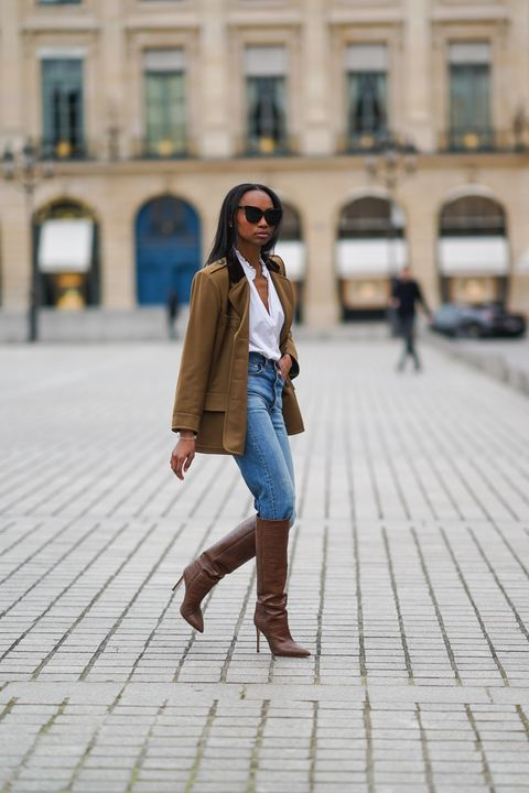 paris, france   january 26 emilie joseph wears sunglasses, a khaki military jacket from saint laurent ysl, a white shirt  blouse from zara with ruffled collar, blue denim jeans pants from levis, brown high heeled knee high pointy leather crocodile pattern boots from paris texas, on january 26, 2021 in paris, france photo by edward berthelotgetty images