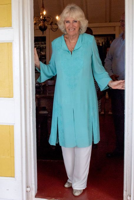 While visiting St. Kitts and Nevis on a royal tour of the Caribbean , Camilla wore a tiffany blue, embroidered caftan with white pants, turquoise drop earrings, and gold ballet flats.