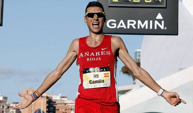 camilo santiago cruaz la línea de meta del maratón de valencia batiendo su marca personal