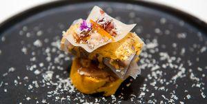 """""""Lingote de pato a la naranja"""" . Subcampeón de Euskadi Amstel Oro 2016  Autor: Mikel Muñoz. Bar Gran Sol (Hondarribia)  Es una oda al pato: asado a baja temperatura, confitado, en jamón, una salsa reducida con elementos del pato con naranja, y perlas de jengibre. Todo ello rematado con una teja de naranja y polvo de las pieles del propio pato.   Necesitas: Pato desmigado, obleas de arroz, pasta para rollito de primavera, salsa de pato, salsa de naranja, flores y tomillo limonero, foie, pan de naranja, perlas de jengibre, chocolate a la naranja, tiras de naranja confitados.   Elaboración: Para el lingote: hacer lingotes de 25 gramos y rellenar con 5 gramos de cáscara de naranja. Cubrir con obleas de arroz remojadas.  Para la teja: hacer unas láminas fritas con pasta de rollito de primavera. Sobre éstas colocar mollejas, jamón de pato, perlas de jengibre, las tiras de naranja y las flores.  Para la salsa de naranja: reducir el zumo y añadir miel. Tiene que quedar textura de salsa.  Para la salsa de pato: hacer un caldo concentrado con cuellos, carcasa y huesos. Preparar verdura pochada y remojar con el caldo.  El oro a la naranja: juntar el aceite con el polvo de oro y la esencia de naranja.  Pan de naranja: cortar y tostar. Untar con foie.  Presentación: Montar la teja. Hacer el lingote. Sobre el pan colocar el lingote saltear con las salsas, poner la teja y rallar con chocolate de naranja."""