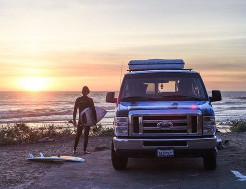 man at beach with surfboard next to an escape campervan