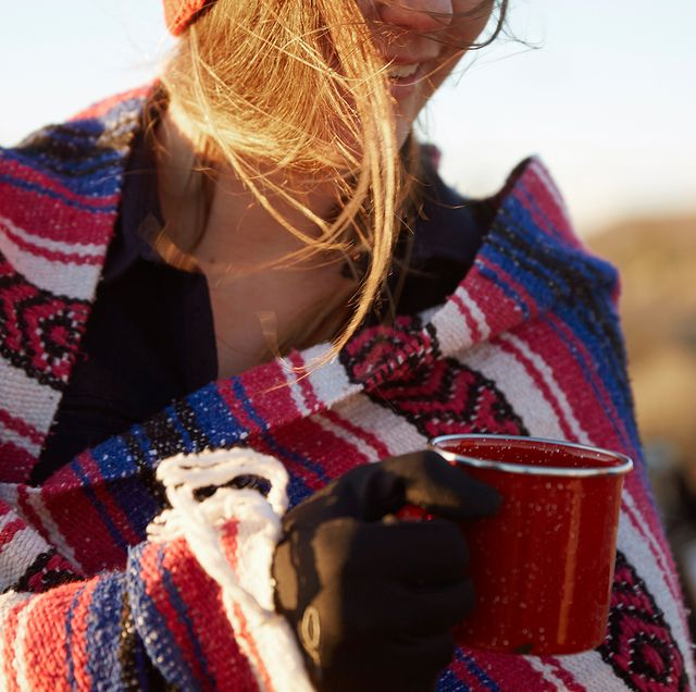 woman wrapping in camping blanket holding mug