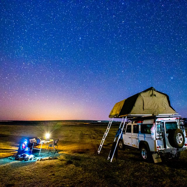 woman building a fire next to land rover with tent on top under a starry sky