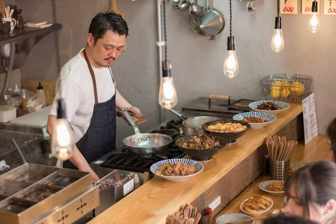 Candid Wide View of Asian Bar Owner Cooking Food in the Kitchen