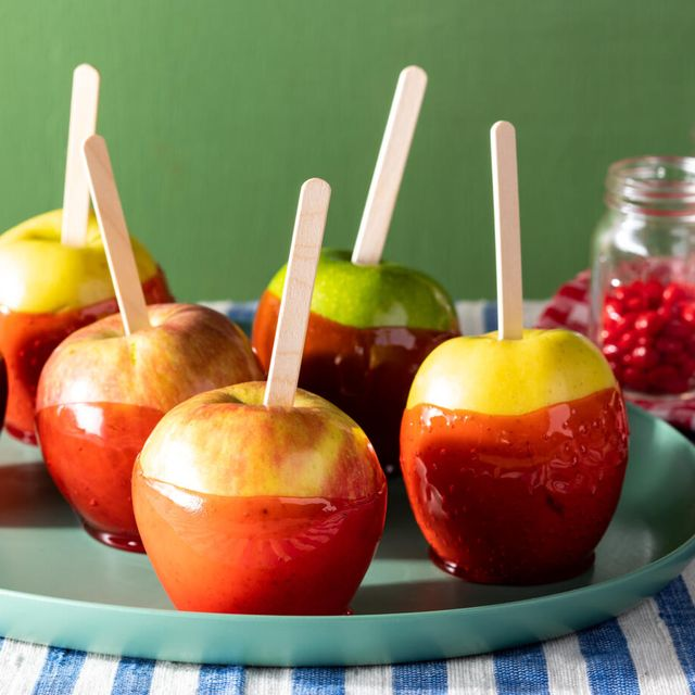 candied apples coated with red cinnamon candy with popsicle sticks on blue striped linen with cinnamon candy in the background