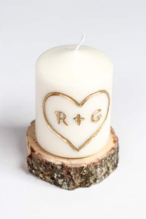 white candle with an engraving that says r  g in gold