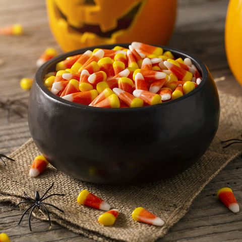 bowl of halloween candy corns with jack o' lanterns and spider decoration on rustic wood table