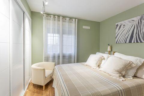 dormitorio con paredes en color verde y armario empotrado con puertas correderas blancas