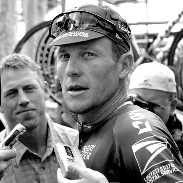 lance armstrong being interviewed by reporters on race day during his time with the us postal service team