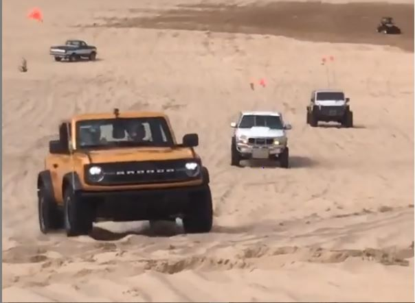 a 2021 ford bronco traverses sand dunes