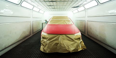 Car covered with mask stands in the spray booth