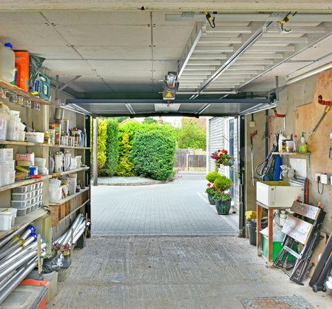 ewd914 car garage shelves interior of domestic house garage secure car park  storage of gardening sundries maintenance tools tins  cans essex england uk