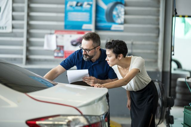 car insurance claims process  insurance agent explaining damage of car exterior to customer at auto repair center business hour 247 service coverage customer service, quality of service