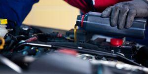 Car mechanic changing engine oil