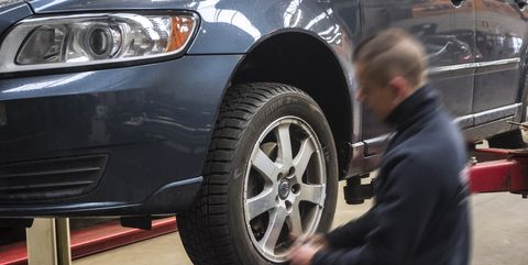 car mechanic changing summer tyres for winter tires on wheels of vehicle in tire centre