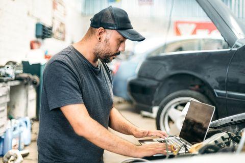car mechanic using computer in auto repair shop