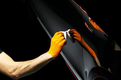 carro polonês cera trabalhador mãos polir carro polir e polir veículo com cerâmica carro detalhando homem segura um polidor na mão e lustra o carro com nano ferramentas de cerâmica para polir