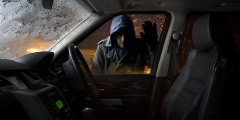 car thief looking into parked car