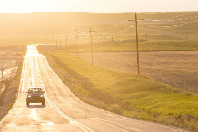 car traveling on long straight open highway at sunset