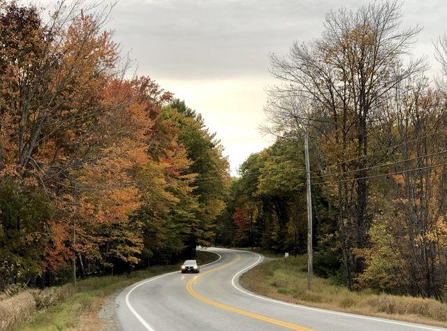 car travels down roadway near augusta, maine usa during autumn