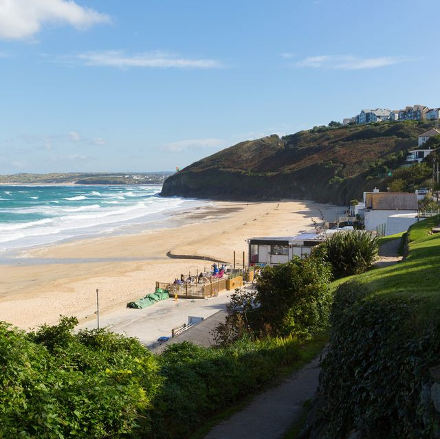 south west coast path carbis bay cornwall england near st ives with a sandy beach and blue sky on a beautiful sunny day
