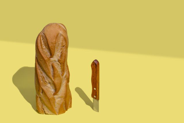 half loaf of bread and a knife on yellow background