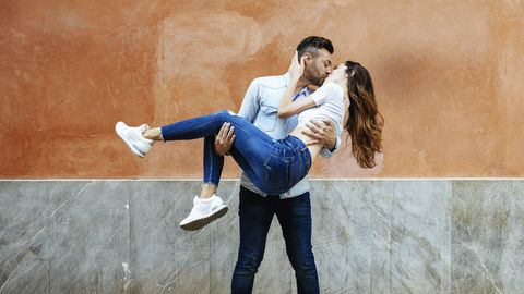Carefree couple in love kissing in front of a wall outdoors