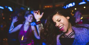 Carefree, enthusiastic young female millennial dancing, partying in nightclub