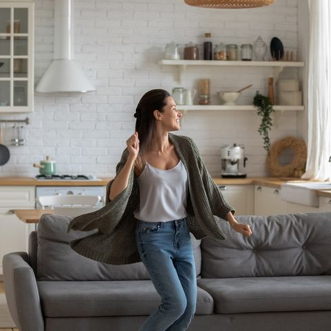 carefree happy young woman dancing alone in modern kitchen