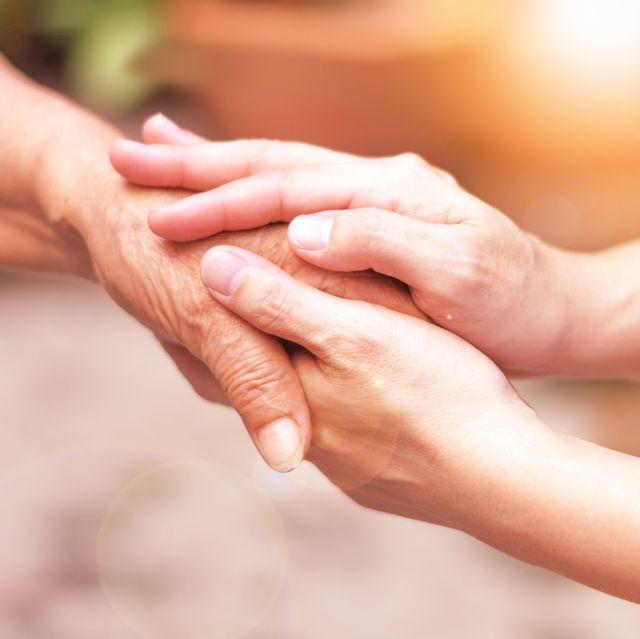 caregiver, carer hand holding elder hand in hospice care philanthropy kindness to disabled concept