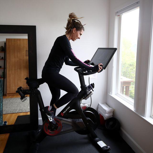 woman riding a peloton bike at home