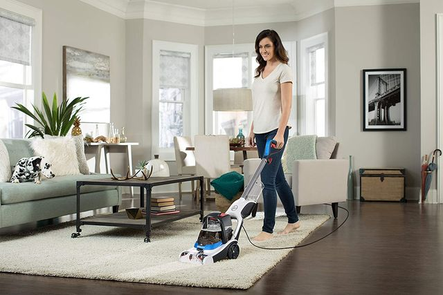 woman using carpet cleaner to clean rug in living room, dog on teal couch