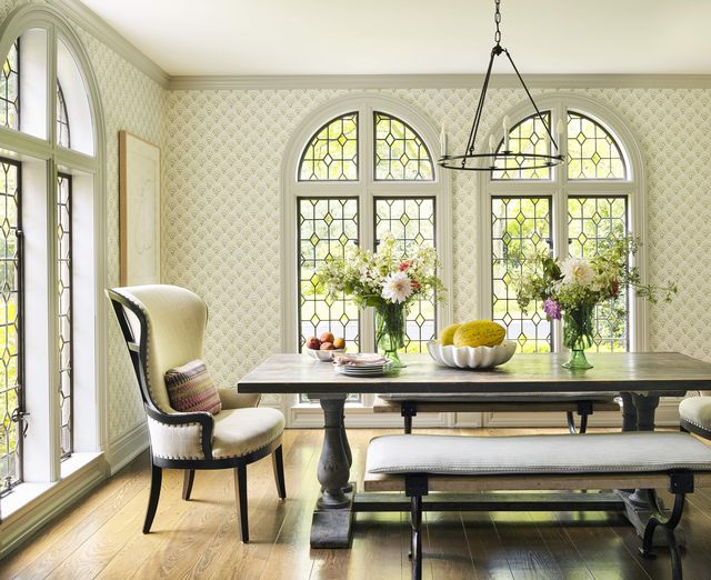 a long table with benches and chairs at the ends in a light filled sunny breakfast room