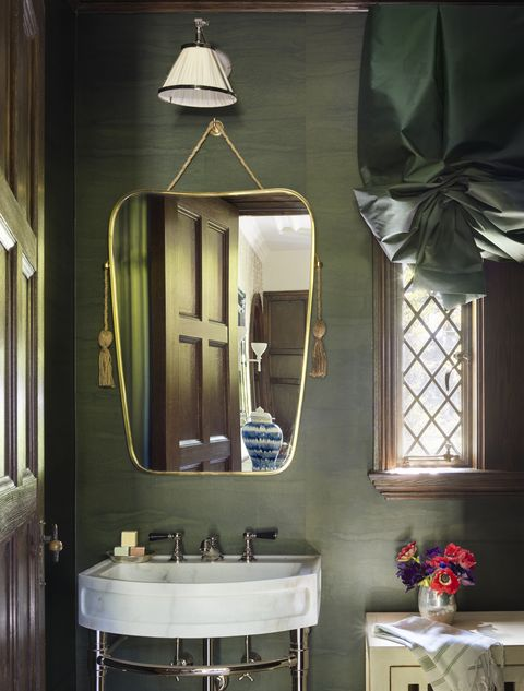 a polished nickel and stone washstand with tasseled, art deco–inspired mirror