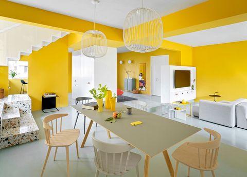 Comedor y salón con paredes de color amarillo y escaleras de terrazo