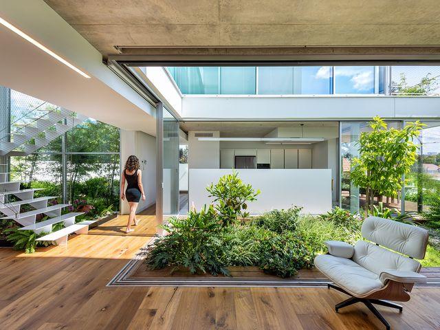 una casa con una arquitectura moderna y un patio con jardín