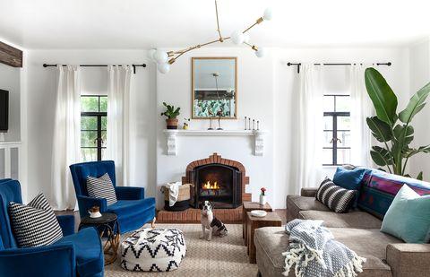 salón con chimenea de piedra, dos butacas de terciopelo azul, un sofá gris y una lámpara de techo mid century