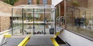 Casa reconstruida con invernadero-huerto urbano en el patio, elevado sobre vigas, de dmvA